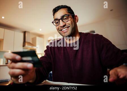 Souriant de course mixte homme d'affaires faire des achats en ligne tenant des crédits carte