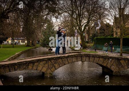 Royaume-Uni, Gloucestershire, Bourton on the Water, couple sur le pont prenant selfie avec arbre de Noël à River Windrush