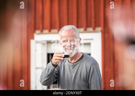 Homme souriant ayant du vin rouge