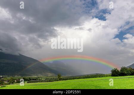 Un grand arc-en-ciel émerge des nuages au-dessus d'un champ de pommes planté à Val Venosta, Prato allo Stelvio, Italie