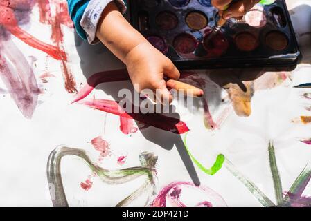 La création de la fille peint sur le sol avec la peinture des enfants un dessin abstrait de bébés sans formes.