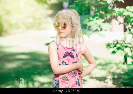 Jeune fille posant dans des lunettes de soleil de forme pentagonale rose fantaisie en plein air. Mignon sérieux pensif élégant enfant caucasien avec de longs cheveux blond portant le rose Banque D'Images