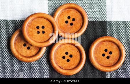Boutons ronds de couture marron en bois isolés sur fond textile. Vue de dessus . Gros plan. Macro.