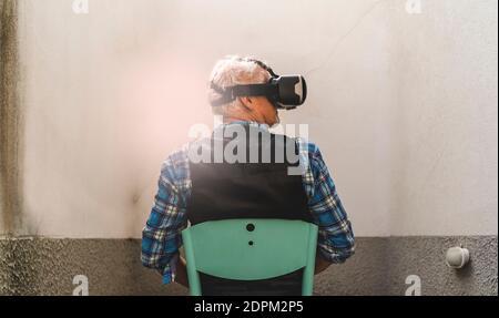 Vue arrière de l'homme senior regardant à travers le simulateur de réalité virtuelle tout en étant assis sur la chaise