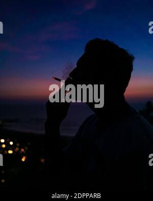 Silhouette Man fumant de la cigarette contre le ciel pendant UN coucher de soleil de Moody.
