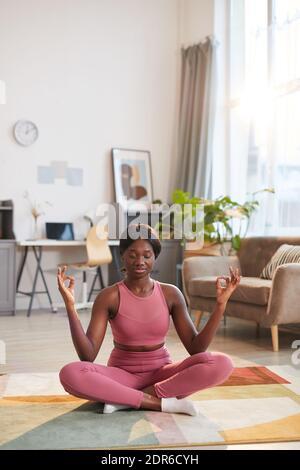 Portrait vertical de la jeune femme afro-américaine portant des vêtements de sport roses pendant entraînement de yoga à la maison