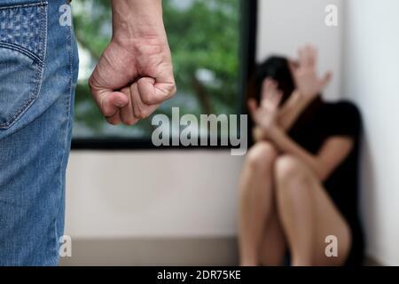 Mi-section de l'homme harcelant la femme assise contre la fenêtre à la maison