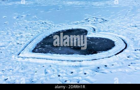 Grand coeur sur un lac gelé recouvert de neige. Hiver romantique fond. Cœur glacé, la Saint Valentin et le concept romantique, l'espace de copie