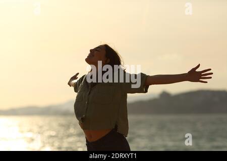 Silhouette d'une femme excitée qui s'étire les bras sur la plage au coucher du soleil