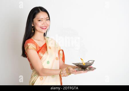 Portrait of young mixed race Indian Chinese femme en sari traditionnel robe, holding diya lampe à huile, sur fond uni. Banque D'Images