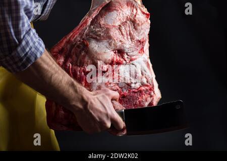 boucher, en tenant la viande de porc et la hache de cuisine entre les mains, sur fond noir. Banque D'Images