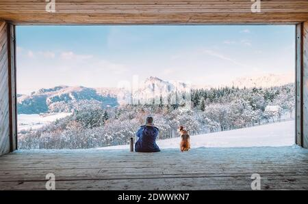 Femme avec thermos ballon assis avec son chien beagle dedans le grand hangar en bois avec une immense fenêtre panoramique et vue sur le paysage de montagne enneigé