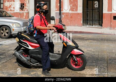 Homme à cheval vespa portant un masque facial, Merida Mexico