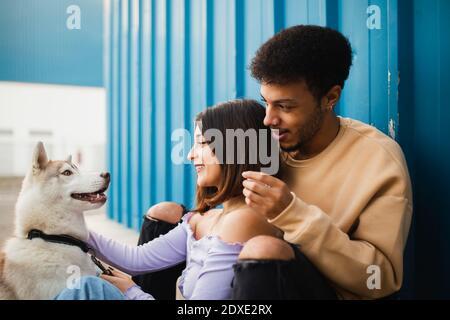 Couple souriant assis avec un chien tout en s'appuyant sur un mur bleu Banque D'Images