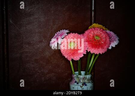 Gros plan du vase à fleurs roses contre le mur