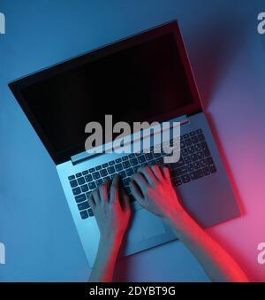 Hacker. Travailleur en ligne. Travail de nuit à l'ordinateur portable. Les mains des femmes tapent sur un ordinateur portable. Néon bleu rouge