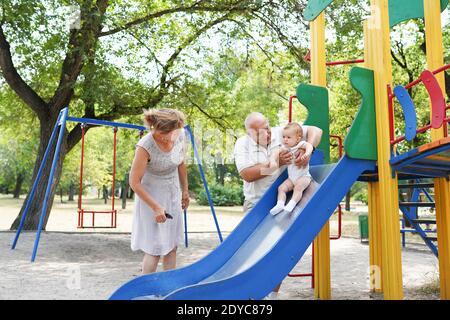 Grands-parents et petite-fille marchant dans le parc Banque D'Images