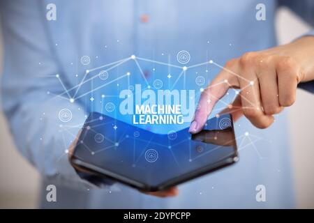 Businessman holding a smartphone pliable avec l'apprentissage automatique de l'inscription, la nouvelle technologie concept