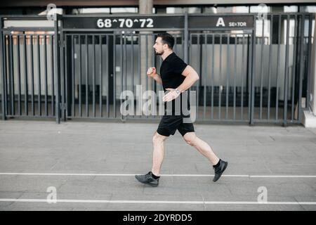 Séance d'entraînement concentrée de coureur masculin le matin. Concept de style de vie urbain. Homme de sport en noir vêtements de sport et baskets de jogging en plein air