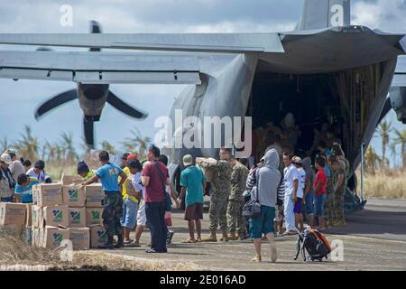Guiuan, province de l'est du Samar, République des Philippines (nov 16, 2013) des marins du porte-avions déployé par l'avant de la Marine américaine USS George Washington (CVN 73), aux côtés de Marines et de civils philippins, aident à décharger des approvisionnements d'un Hercules HC-130 de l'Escadron de soutien de l'escadre maritime (SMSS) 172 à l'appui de l'opération Damayan. Le groupe de grève George Washington appuie la 3e Brigade expéditionnaire maritime pour aider le gouvernement philippin à répondre aux séquelles du Super Typhon Haiyan en République des Philippines. Photo par US Navy via ABACAPRESS.COM