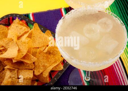 Fête mexicaine et thème de la fête de Cinco de Mayo avec table traditionnelle ou serape, deux verres de margarita sur les rochers et puce de tortilla