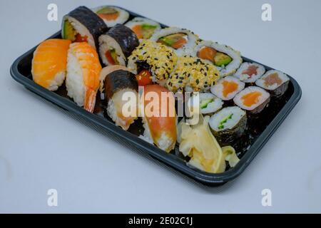 différents types de sushis se trouvent côte à côte sur un plaque noire
