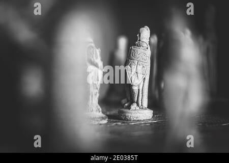 Un portrait noir et blanc d'un soldat en pierre blanche sur un échiquier en pierre face d'un soldat noir et de son armée derrière lui. Prêt pour le duel entre mi