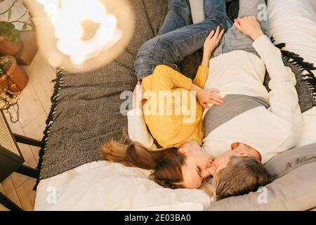 Histoire d'amour. Dans l'amour couple baiser sur le lit dans la soirée. Vue de dessus, ampoule au premier plan. Jaune et gris 2021.