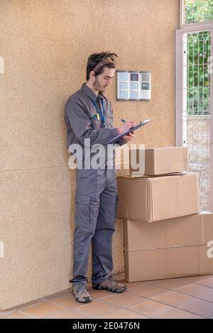 Messenger avec masque livre des paquets à la porte à côté de le portier