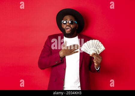 Un homme afro-américain choqué tient la main sur le cœur et se secoue de l'excitation, montrant une énorme quantité d'argent, gagnant le prix, se tenant au-dessus de rouge