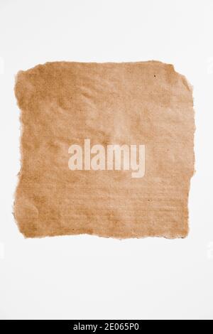 Morceau de papier brun carré déchiré avec bords déchirés isolés sur blanc.