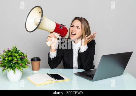 Angry businesswoman yelling avec haut-parleur de bureau