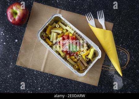 Du dessus de délicieux macaroni au ketchup et au fromage dans un récipient pour les plats à emporter sur la table avec la pomme
