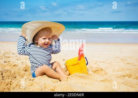 Un petit garçon heureux s'assoit sur la plage et porte un grand vêtement jeu de chapeau de paille avec seau en plastique Banque D'Images