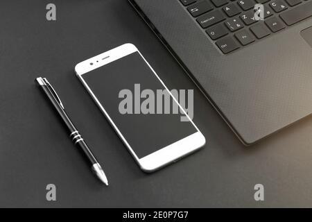 Stylet, téléphone portable et clavier d'ordinateur portable sur un bureau gris/noir - vue du dessus