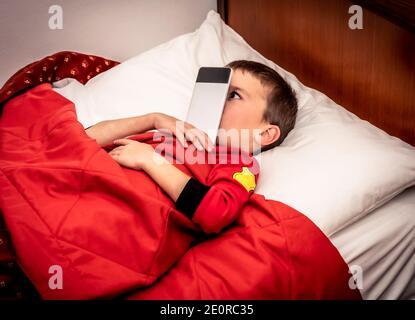 L'enfant sous les couvertures dans le lit joue et blague avec son téléphone portable collé à son nez, avant de s'endormir.
