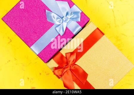 Boîtes-cadeaux carrées de couleur sur fond de béton, plat, vue de dessus Banque D'Images