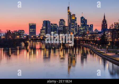 Horizon de Francfort dans la soirée au coucher du soleil. Bâtiments en hauteur du quartier financier et de la rivière main avec réflexions. Maisons éclairées