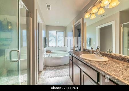 Cabine de douche et meuble-lavabo simple dans la salle de bains attenante avec mur blanc