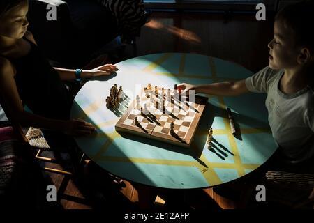 Une jeune fille regarde comme son petit frère se déplace une pièce en jouant aux échecs ensemble assis à une table basse baignée de lumière du soleil. Banque D'Images