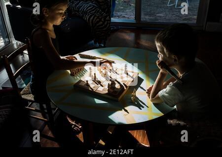 Une jeune fille et son petit frère jouent ensemble aux échecs assis à une table basse baignée de lumière du soleil. Banque D'Images