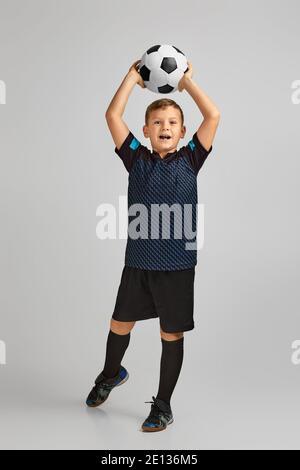 petit garçon joueur de football en uniforme avec ballon sur fond de studio. enfant rêve de devenir joueur de football.