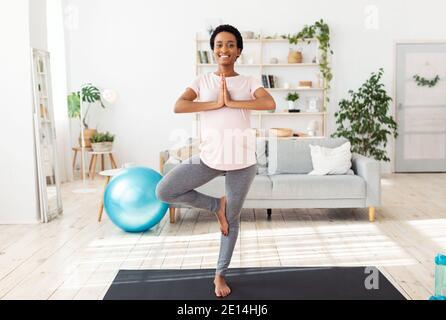 Jeune femme expectative faisant son entraînement de yoga du matin, debout dans la pose d'arbre, se sentant paisible à la maison