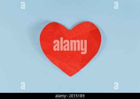 Coeur en papier rouge cassé avec lignes pliantes sur fond bleu. Concept pour coeur brisé ou malade Banque D'Images