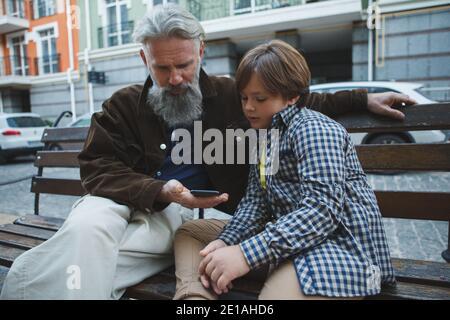 Homme âgé utilisant un smartphone avec l'aide de son petit-fils, assis sur un banc dans la ville