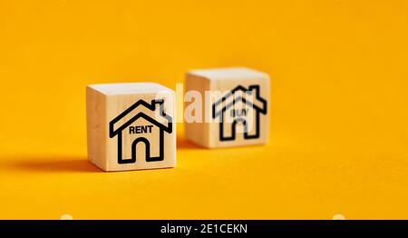 Icônes maison sur des cubes en bois avec options d'achat ou de location. Décision de louer un concept immobilier.