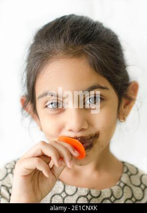 Petite fille indienne souriante aime manger un bâton de glace avec des taches autour de sa bouche. Banque D'Images