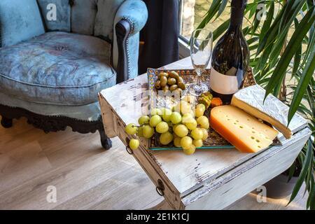 plateau de fromages avec raisins et vin sur une table près d'une fenêtre avec une chaise confortable. Décoration intérieure moderne