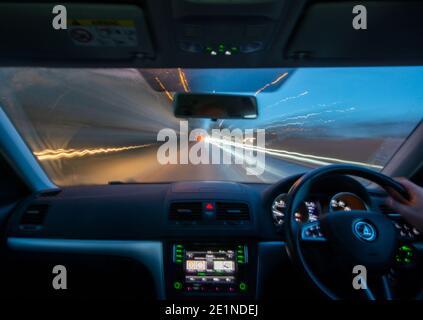 Vue longue exposition depuis l'intérieur d'une voiture roulant le long d'une route à l'aube avec des sentiers légers de la circulation venant en sens inverse