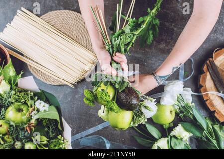 Hobbies et activités, arts et métiers pendant le coronavirus. Fleuriste femme faire fruit comestible bouquet. Naturel, arrangement de fleurs, tours de fleuriste